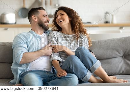 Happy Married Young Couple Hugging, Sitting On Couch Together