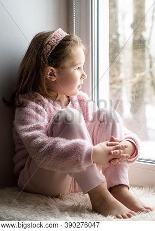 Kid Sitting On Windowsill At Home Looks Out Window To Snow, Portrait Of Pretty Little Girl On Fur Ru