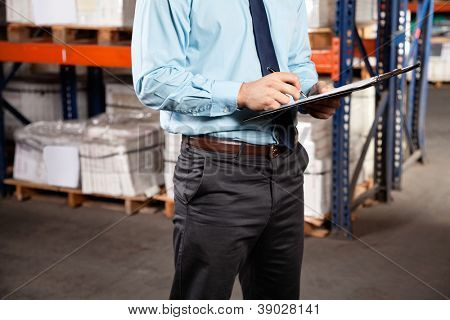 Midsection of male supervisor writing on clipboard at warehouse