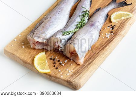 Raw Pollock Fish On A Wooden Board With Lemon And Spices
