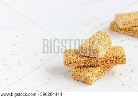 Chikki - Traditional Indian Sweet. Sesame Brittle On White Wooden Background. Copy Space