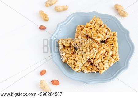 Plate Of Traditional Peanut Brittle Candy Pieces. Sweets On A White Wooden Background.
