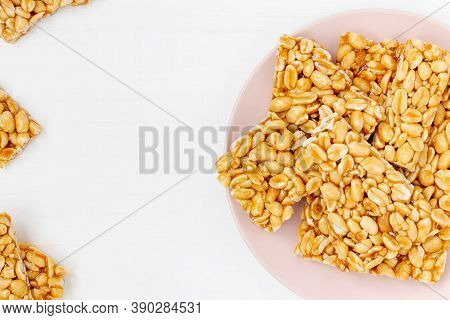 Plate Of Peanut Brittle Candy Pieces On A White Wooden Background. Top View, Copy Space