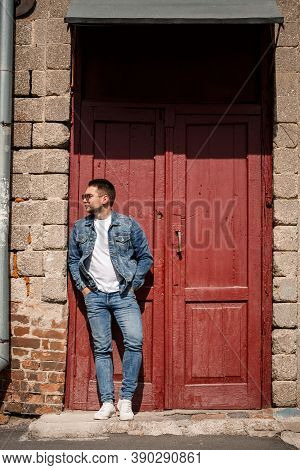 Handsome Man With A Beard In A Denim Jacket And Denim Pants Stands Near Red Vintage Doors. Grown Guy