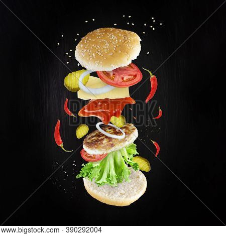 Levitating Cheeseburger Components On Dark Background. Sandwich Ingredients Floating In The Air: Red