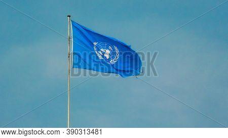 Geneva, Switzerland - Aug 16, 2020: Flag With Emblem Of United Nations Building Isolated Against Blu