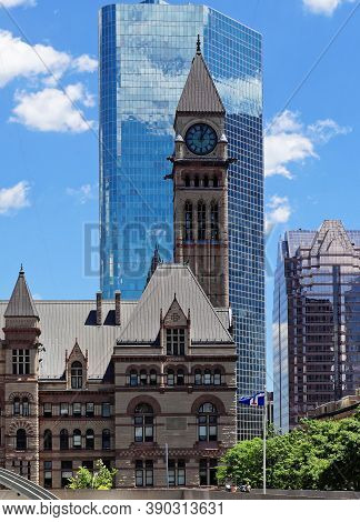 Toronto, Canada - 06 27 2016: The Clock Tower Of The Old City Hall In Front Of Glassy Wall Of Cadill
