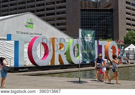 Toronto, Canada - 06 27 2016: People Walking In Front Of Toronto Sign And The Concert Hall Pavilion
