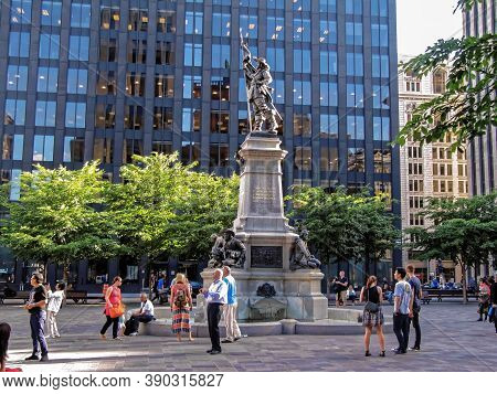Montreal, Canada - 06 24 2016: The Maisonneuve Monument In Front Of 500 Place Darmes Building In Hea
