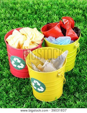 Recycling bins on green grass