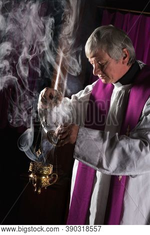 Incense in a burner and catholic priest