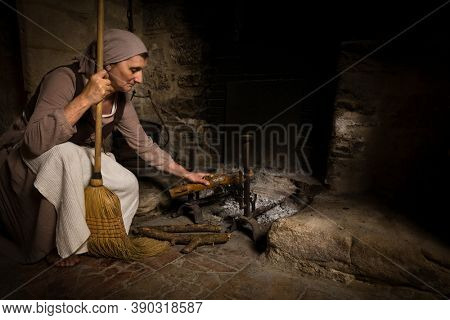 Woman in historical outfit adding wood logs to the fireplace in the kitchen of a property released medieval castle