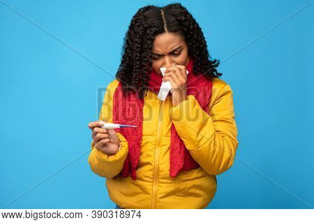 Ill African American Lady Holding Thermometer Having Fever Sneezing In Paper Tissue Standing Over Bl