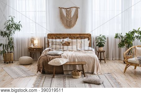 Rustic Home Design With Ethnic Decoration. Bed With Pillows, Wooden Furniture, Plants In Pots, Armch