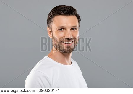 Handsome Bearded Middle-aged Man Smiling At Camera Over Grey Studio Background, Copy Space. Cheerful