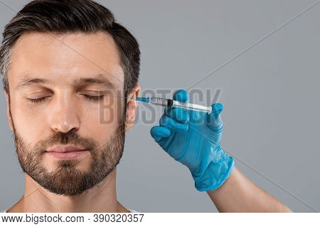 Middle-aged Bearded Man Getting Anti-wrinkle Injection In Eye Zone Over Grey Studio Background. Cosm
