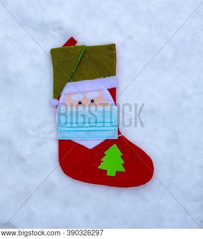 A Christmas Sock Ornament Decoration With A Face Mask On Snow. Concept: Covid-19, Coronavirus During