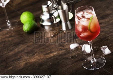 Campari Tonic Alcoholic Cocktail With Red Bitter, Tonic, Lime And Ice. Old Wooden Table Background,