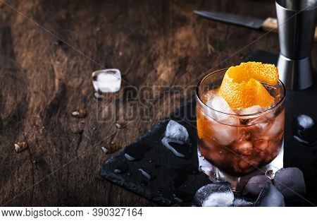 Red Cocktail With Dry Vermouth, Bitter, Soda, Orange Zest And Ice, Wooden Bar Counter Background, Ba