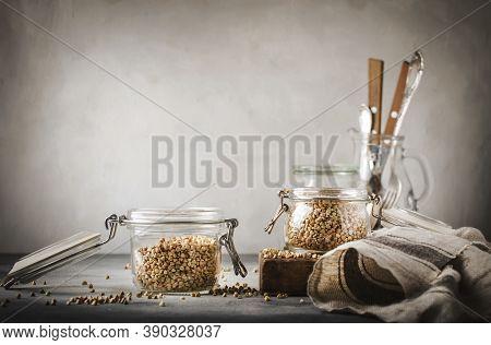 Uncooked Green Buckwheat Groat In Glass Jar, Healthy Vegetarian Food On Gray Kitchen Table, Copy Spa