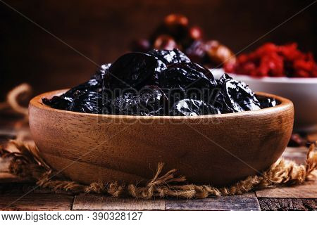Dried Sweet Prunes Or Dark Plums In Bowl On Wooden Background, Selective Focus