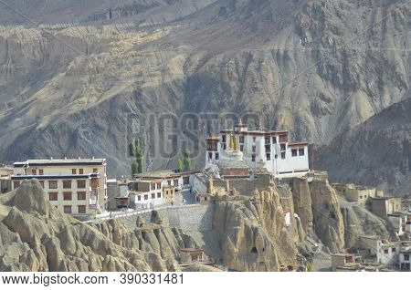 White Monastery Buildings Contrast Against Barren Mountain Slopes. They Are On Top Of A Steep Hill,