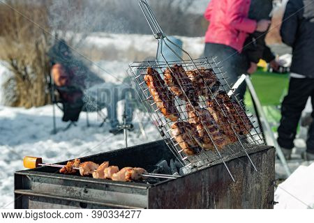 Winter Barbecue Outdoors, Grill Steak And Fork With Meat Over Hot Coals In A Bbq At Campside Cookout