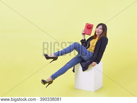 Full Length Portrait Attractive Young Woman Holding Gift Levitating Isolated Yellow Background