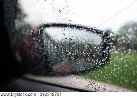 Unstable View From Car Side Mirror And Wet Car Window In Drizzle With Blurred Reflection Through Rai