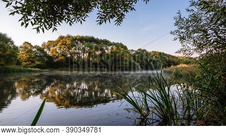 Summer Or Autumn Sunrise Over The River. Calm Water Flow, Morning Fog And Birds. Natural Beauty Of P