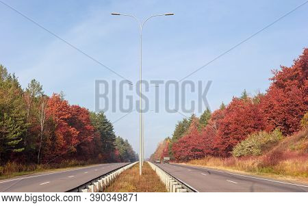 Straight Section Of The Motorway With Forest On Both Sides At Autumn, View From Grass Median Strip W