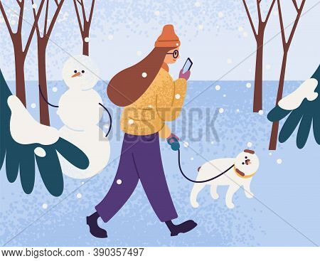 Young Woman In Warm Outerwear Walking Dog In Park And Looking In Smartphone. Female Character With P
