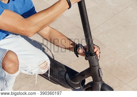 Young Man Unfolding Electric Scooter  Close Up