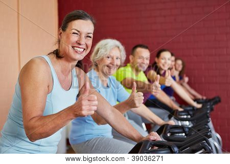 Happy group in fitness center in spinning class holding the thumbs up