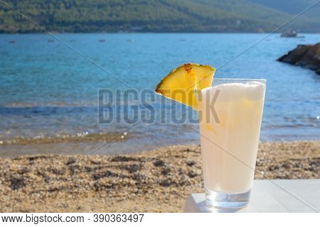 Delicious Pina Colada Cocktail In A Glass With A Slice Of Pineapple On The Background Of The Sea. Re