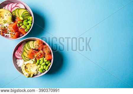 Poke Bowl With Salmon, Rice, Avocado, Edamame Beans, Cucumber And Radish In A Gray Bowls, Top View.
