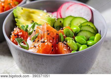 Poke Bowl With Salmon, Rice, Avocado, Edamame Beans, Cucumber And Radish In A Gray Bowl. Hawaiian Ah
