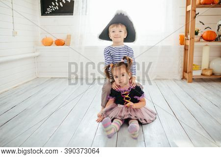 Boy In A Pirate Costume And A Girl In A Witch Costume Celebrates Halloween At Home