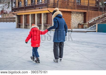Young Mother Teaching Her Little Son Ice Skating At Outdoor Skating Rink. Family Enjoy Winter On Ice