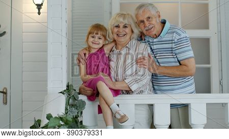 Happy Senior Grandfather And Grandmother Couple With Granddaughter Waving Hand, Smiling, Saying Hell