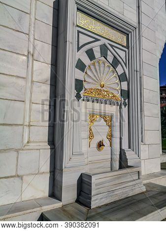 Turkey, Ankara - October 23, 2019: Gilded faucet in the white marble wall of the Melike Hatun Mosque in Ankara, outdoor. Delightful rich decor of the facade of a Turkish Muslim temple
