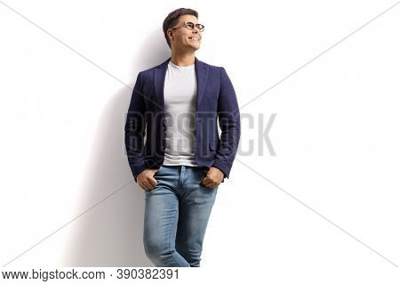 Handsome young man in jeans and suit leaning on a white wall and looking up isolated on white background