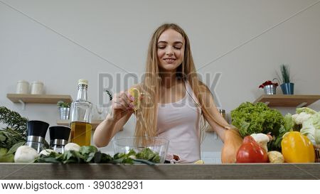 Cheerful Vegan Girl Cooking Salad With Raw Vegetables, Adding Lemon Juice. Young Woman Squeeze A Lem