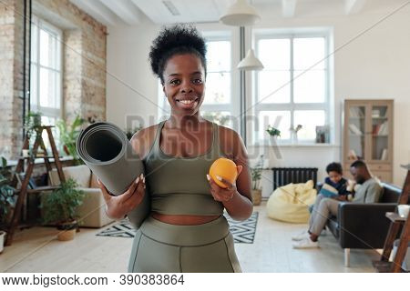 Healthy young African fit woman with toothy smile holding rolled mat and fresh orange while going to have training at home against her family