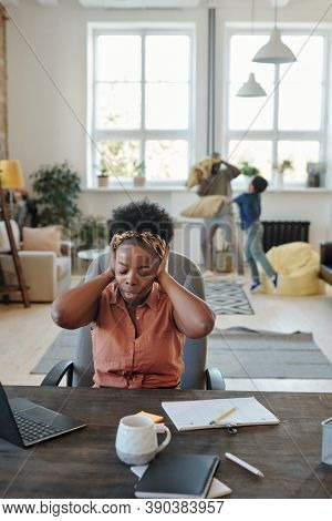 Young annoyed African woman with headache touching head while sitting by table in front of laptop against her husband playing with little son