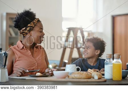 Happy young woman of African ethnicity having homemade dessert by table and looking at her cute cheerful little son during breakfast