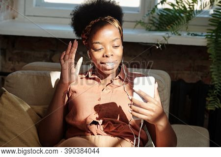 Young cheerful restful woman of African ethnicity looking at smartphone screen and waving hand while talking to someone through video chat