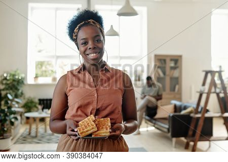 Young happy African female with homemade waffles looking at you with toothy smile while standing against her husband sitting on couch