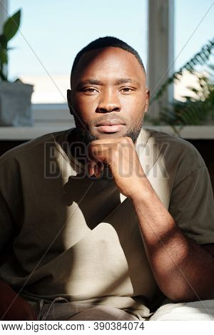 Young serious man of African ethnicity looking at you while sitting in front of camera against window with domestic plants in home environemnt