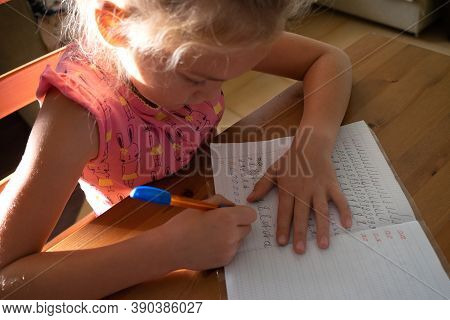 Little First-grader Girl Makes Writes Letters In A Copybook